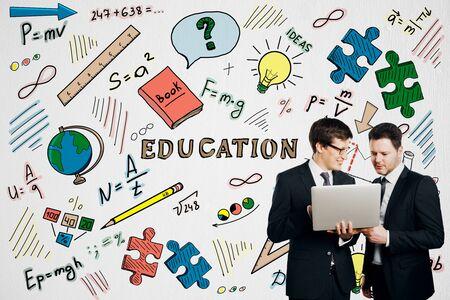 Glückliche Geschäftsleute mit Laptop mit kreativer Bildungsskizze auf weißem Betonmauerhintergrund Spott oben. Wissen, Teamwork und Seminarkonzept