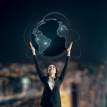 Global business concept with businesswoman holiding world map with blue glowing lines around at blurry city view background. Stock Photo