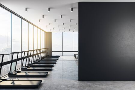 Big blank black wall in a modern gym with fashion treadmills, concrete floor and big clean windows in a skyscraper. Health concept. 3D Rendering