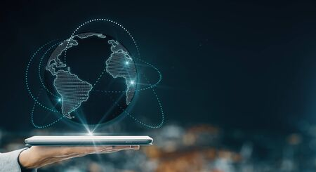 Global telecommunication concept with human hand holding digital tablet projecting world map with glowing lines around at blurry city view background.