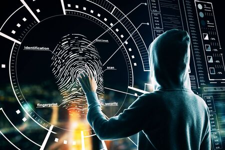 Malware and security concept with back view hacker pushing on fingerprint on digital screen with cyberspace icons. Stok Fotoğraf