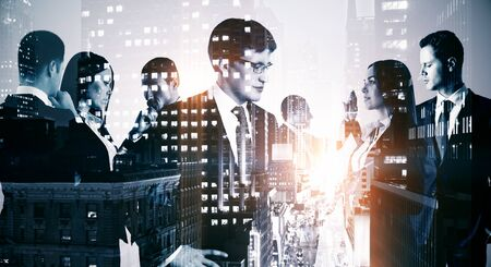 Double exposure of group of business people working on the background of the city