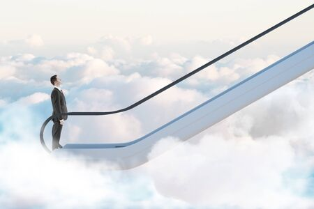 Road to success concept with businessman going up by escalator among white clouds.