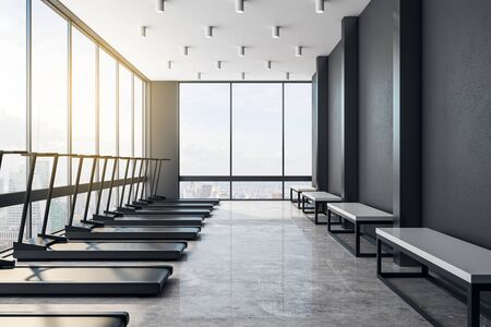 Modern light gym interior in skyscraper with black treadmills, black walls, concrete floor and benches and city view from big windows. 3D Rendering