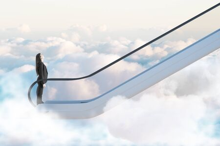 Road to success concept with businesswoman going up by escalator among white clouds.