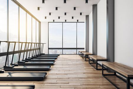 Empty gym with modern interior. Black treadmills, wooden floor and benches, big windows and city view. 3D Rendering 写真素材