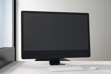 Black blank screen of black computer monitor on white table in light office. 3D Rendering