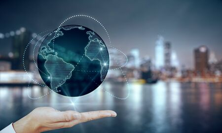 Global internet network concept with man hand projecting world map with glowing lines around at blurry city skyline view background. Stock Photo
