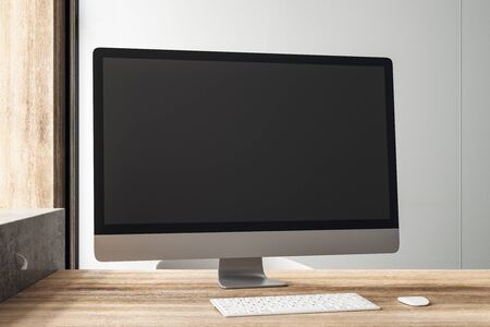 Blank black computer monitor on wooden table in loft style office at sunrise. 3D Rendering
