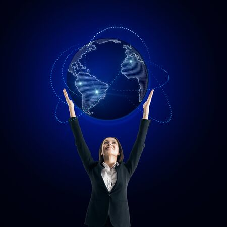 Global business concept with businesswoman holiding world map with blue glowing lines around at dark wall background. Stock Photo