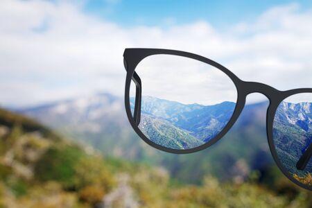 Vista creativa della natura attraverso gli occhiali. Sfondo sfocato. Concetto di visione