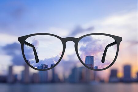 Creative bright city view through eyeglasses. Blurry background. Vision concept