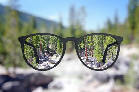 Creative landscape view though eyeglasses. Blurry background. Vision concept Stock Photo