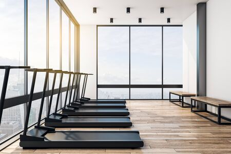 Modern light big empty gym with black treadmills, wooden floor and benches in a skyscraper with city view. Fashion sport concept. 3D Rendering