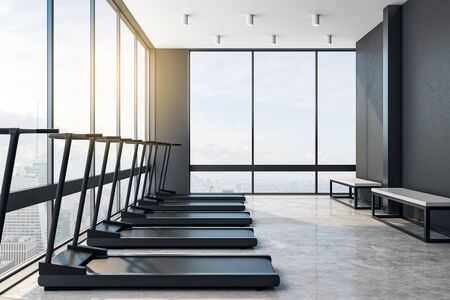 Modern light big empty gym with black treadmills, concrete floor and benches in a skyscraper with city view. Fashion sport concept. 3D Rendering Zdjęcie Seryjne