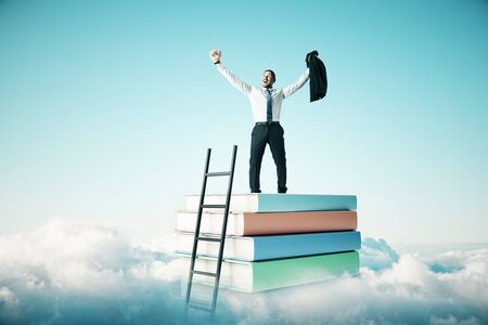 Happy businessman standing on abstract book stack with ladder on sky with clouds background. Education and growth concept