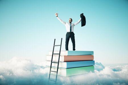Glücklicher Geschäftsmann, der auf abstraktem Buchstapel mit Leiter am Himmel mit Wolkenhintergrund steht. Bildungs- und Wachstumskonzept Standard-Bild
