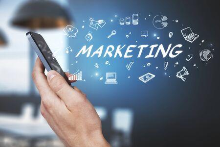 Nahaufnahme der Hand, die Smartphone mit abstrakter Marketingskizze auf verschwommenem Büroinnenhintergrund hält. Erfolgs- und Managementkonzept. Mehrfachbelichtung