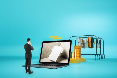 Concepto creativo de compras en línea con el empresario mirando portátil enorme y racks con ropa sobre fondo azul.