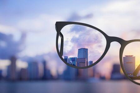 Uitzicht op de moderne heldere stad door een bril. Wazige achtergrond. Visie concept