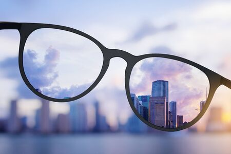 Abstract bright city view through eyeglasses. Blurry background. Vision concept