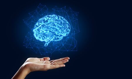 Hand holding creative glowing polygonal brain on blue background. AI and future concept 写真素材