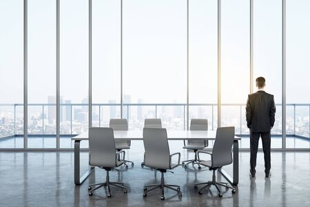 Back view of young businessman in modern meeting room interior with panoramic city view. Workplace and company concept.