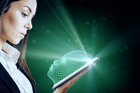Attractive caucasian businesswoman holding tablet with glowing head outline on dark background. AI and face ID concept