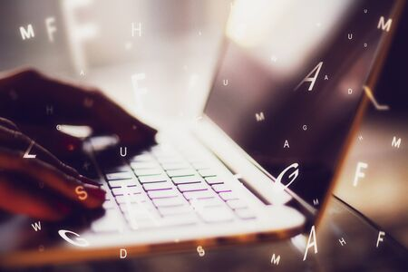 Side view of hands using laptop with abstract letters. Communication and network concept. Multiexposure Stock Photo