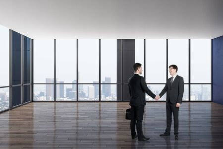 Businessmen shaking hands in luxury empty office interior with panoramic city view and daylight. Teamwork concept.