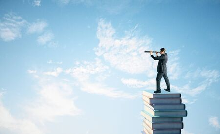 Side view of young businessman standing on books and using telescope to look into the distance on blue sky background with clouds. Research, education and vision concept Фото со стока