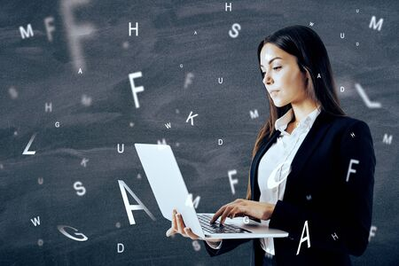 Attractive european businesswoman using laptop with abstract letters on chalkboard background. Communication and network concept. Multiexposure Фото со стока
