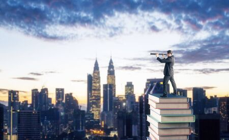 Side view of young businessman standing on books and using telescope to look into the distance on blurry Kuala Lumpur city skyline background with clouds. Research, education and vision concept