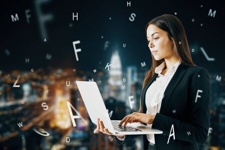 Attractive european businesswoman using laptop with abstract letters on blurry night city background. Communication and network concept. Double exposure