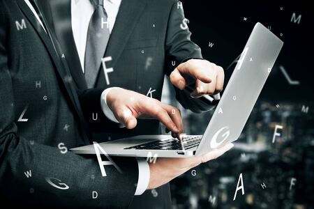 Close up of businessmen hands using laptop with abstract letters on blurry night city background. Communication and teamwork concept. Multiexposure