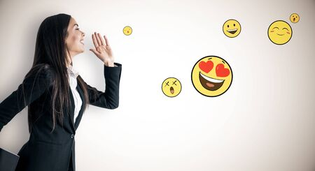 Portrait of happy young businesswoman with emotive smileys on subtle light background. Communication and emotion concept Фото со стока