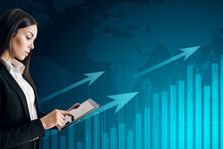 Attractive businesswoman using tablet on glowing blue business chart background with arrows and map. Trade and growth concept