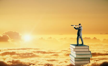 Side view of young businessman standing on books and using telescope to look into the distance on golden sunset sky background with clouds. Research, education and vision concept