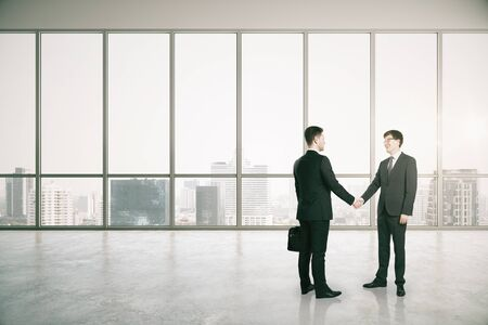 Side view of businessmen shaking hands in modern office interior with city view. Teamwork and partnership concept.