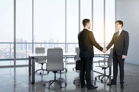 Side view of young businessmen shaking hands in modern meeting room interior with panoramic city view. Workplace and teamwork concept.