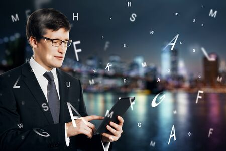 Attractive european businessman using tablet with abstract letters on chalkboard background. Communication and network concept. Multiexposure