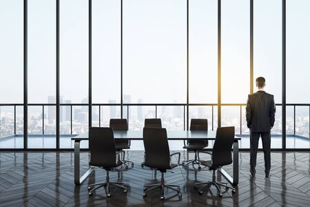 Back view of young businessman in modern conference room interior with panoramic city view. Workplace and company concept. Фото со стока