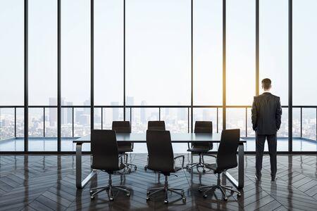 Vista posteriore del giovane uomo d'affari nell'interno moderno della sala conferenze con vista panoramica sulla città. Luogo di lavoro e concetto aziendale.
