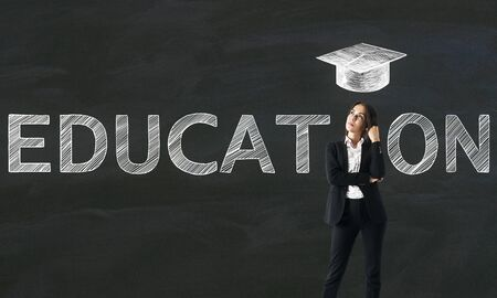Businesswoman with creative educational sketch on chalkboard wall background with graduation cap. Knowledge and education concept Фото со стока