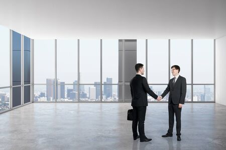 Businessmen shaking hands in modern empty office interior with panoramic city view and daylight. Teamwork concept.
