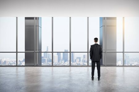 Back view of young businessman looking out of window in modern empty office interior with panoramic city view and daylight. Research concept.