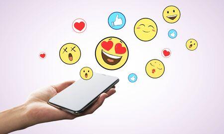 Hand holding smartphone with emotive smileys on subtle background. Communication and emotion concept Banco de Imagens