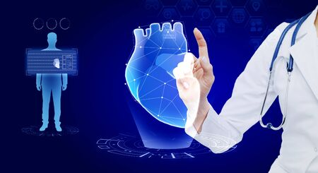 Female doctor using creative glowing blue digital heart futuristic interface hologram on dark wallpaper. Medicine, cardiology and future concept. Multiexposure 스톡 콘텐츠