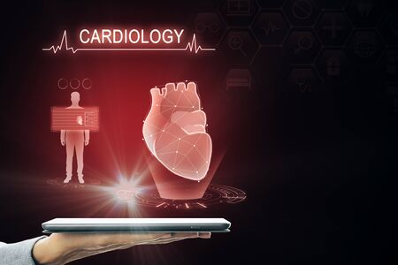 Hand holding tablet with creative glowing red digital heart futuristic interface hologram on dark background. Medicine, cardiology and future concept Stok Fotoğraf