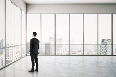 Businessman standing in empty concrete office interior with bright city view. Фото со стока